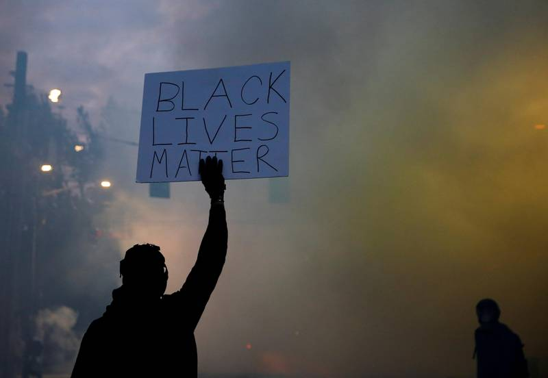 """A person holds a """"Black Lives Matter"""" sign as a heavy cloud of tear gas and smoke rises after being deployed by Seattle police as protesters rally against police brutality and the death in Minneapolis police custody of George Floyd, in Seattle, Washington, U.S. June 1, 2020.  Picture taken June 1, 2020. REUTERS/Lindsey Wasson     TPX IMAGES OF THE DAY"""