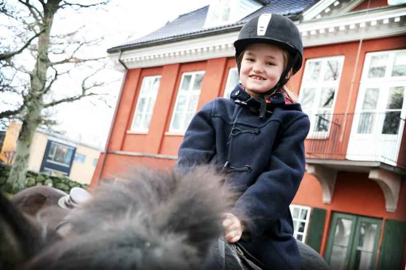 Gun Lovise Tjeldnes Rørosgaard (8) har ridd på ponni før, og synes det var veldig stas. Hun synes ponniene er skjønne, og beskriver rideturen som hundre prosent morsom. Sammen med mamma Ulla og storesøster Liv var hun tilbake på julearrangementet for andre år på rad. FOTO: TONE HELENE OSKARSEN