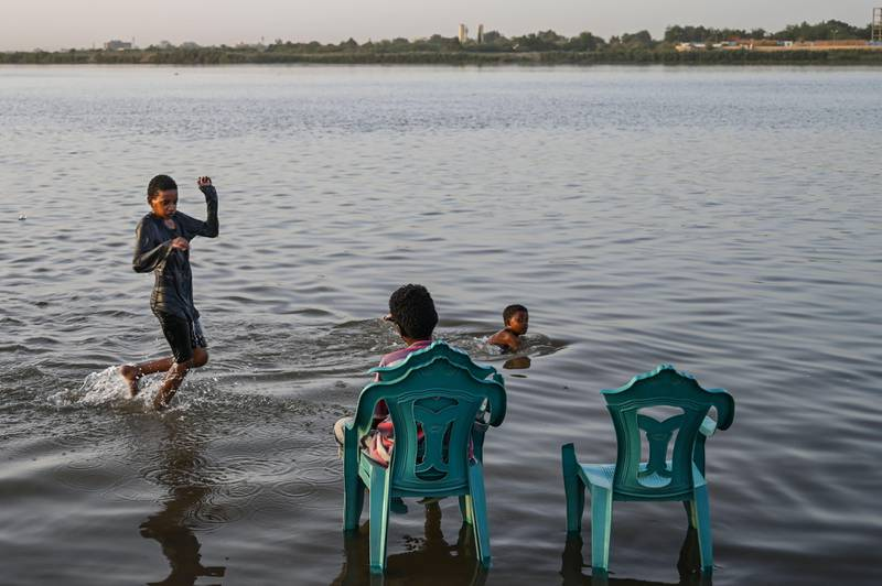 (FILES) In this file photo taken on May 1, 2019, Sudanese boys bath in the shallow waters of the Nile River at Tuti island where the Blue Nile and the White Nile meet to become the Nile river, in Khartoum. - The Nile, Egypt's lifeline since Pharaonic days, faces massive strain from pollution, over-use and climate change -- and now the threat of a colossal dam being built far upstream in Ethiopia. When its London-sized reservoir starts to fill this summer, Egypt fears the mega-project will spell an existential threat to its teeming population of 100 million, 90 percent of whom live along the mighty waterway. (Photo by OZAN KOSE / AFP)