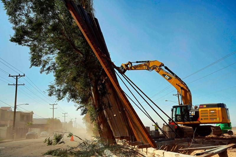 A construction crew works on a fallen section of the US-Mexico border wall as seen from Mexicali, Baja California state, Mexico, on January 29, 2020. - Newly installed panels from the US border wall in Calexico, California, fell over in high winds Wednesday, landing on trees on the Mexican side of the border. (Photo by STR / AFP)