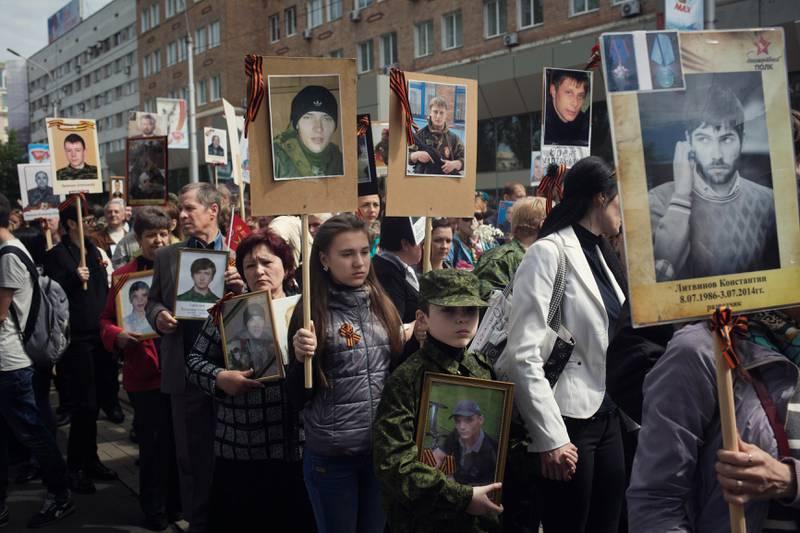 Drepte sønner: I fjor gikk innbyggerne i Donetsk med bilder av bestefedre som tjenestegjorde under andre verdenskrig. Nå er en mye større del av toget bilder av sønner som er falt.