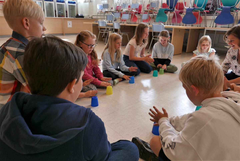 Barna på korpskurset Sommerspill har rytmelek med fargede kopper