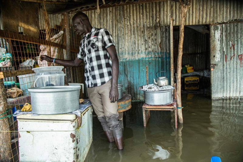 A man prepares tea in front of his shop in a flooded area after the Nile river overflowed after continuous heavy rain which caused thousands of people to be displaced in Bor, central South Sudan, on August 9, 2020. (Photo by Akuot CHOL / AFP)
