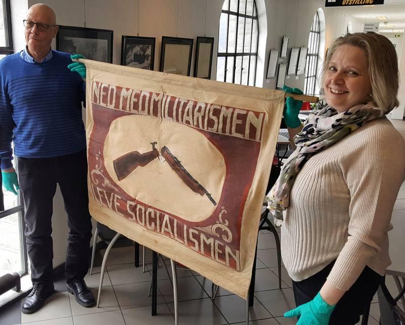 Allerede i 1914 kom det til sammenstøt på Rjukan. Utstillingskurator Gunhild Lurås og lokalhistoriker Tom Nielsen viser fram fanen med det brukne gevær som politimesteren ikke tillot at arbeiderne skulle bruke i 17. mai-toget.