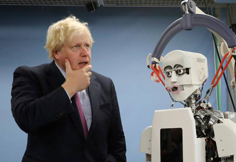 Britain's Foreign Secretary Boris Johnson gestures by a humanoid robot at Research Institute for Science and Engineering at Waseda University's campus in Tokyo Thursday, July 20, 2017. Johnson visited the robotics center at the university, which collaborates with the University of Birmingham. (AP Photo/Eugene Hoshiko, Pool)