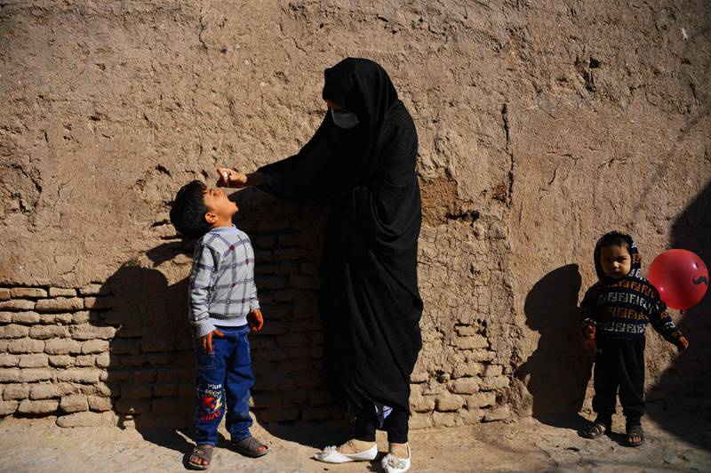 TOPSHOT - A burqa-clad health worker administers polio vaccine drops to a child during a vaccination campaign in the old quarters of Herat October 27, 2020 (Photo by Hoshang Hashimi / AFP)
