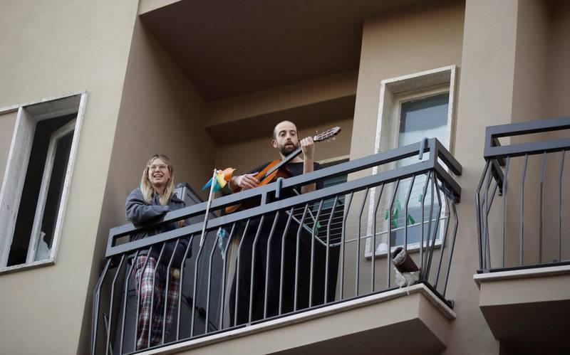 Italienere i karantene spiller gitar, synger og skramler med grytelokk og tamburiner.                                               Foto: NTB scanpix
