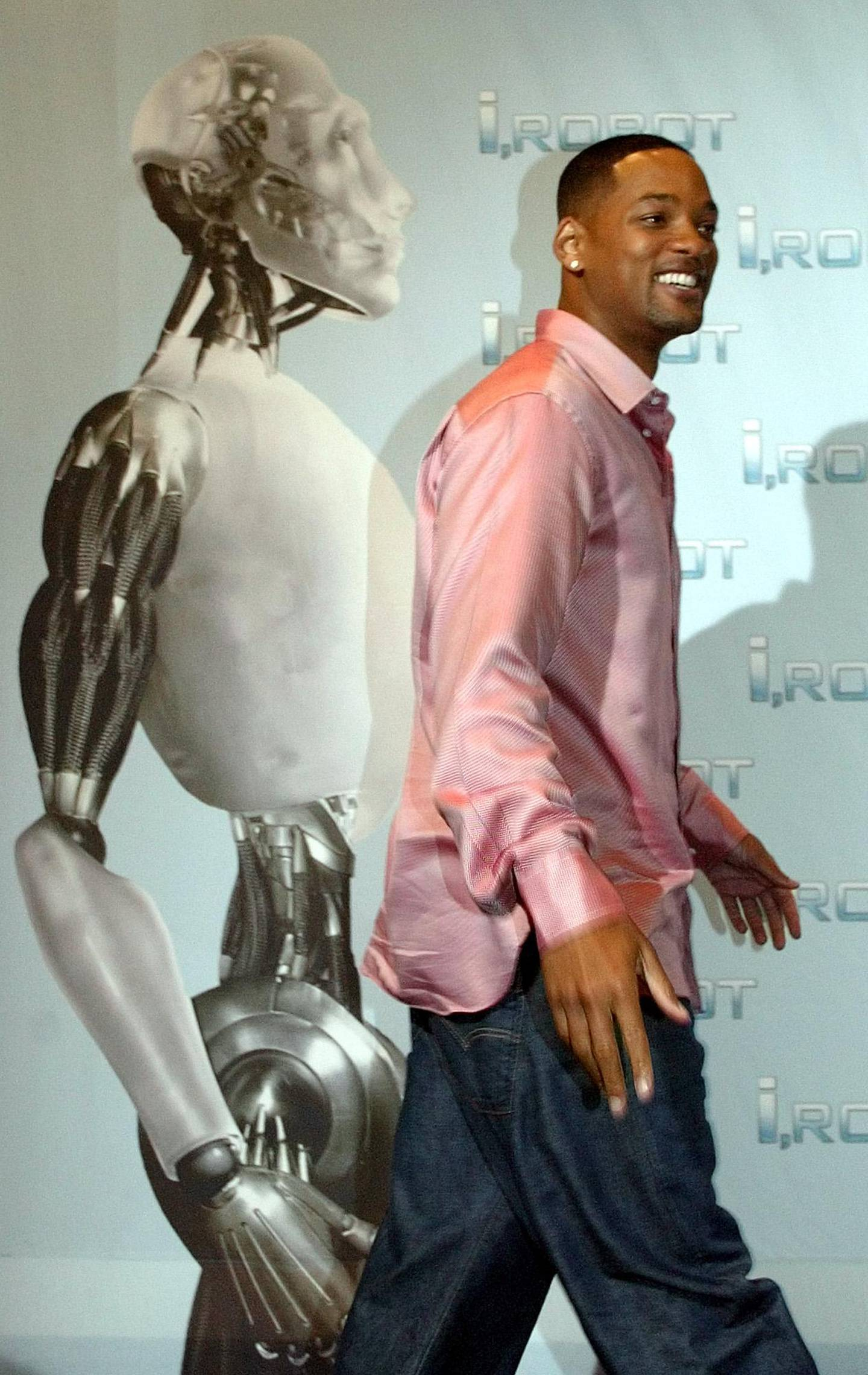 """US actor Will Smith poses for the photographers in front of the movie poster during a photocall prior to the German premiere of his latest film """"I,ROBOT"""" in Berlin Monday, Aug. 2, 2004. (AP Photo/Roberto Pfeil)"""