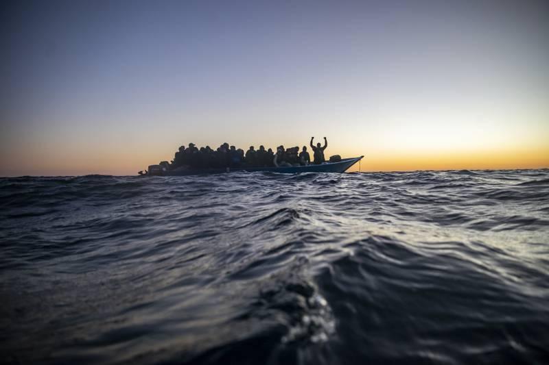 Migranter og flyktninger fra ulike afrikanske land sitter i en overfylt båt, og venter på hjelp av redningsmannskaper fra den spanske hjelpeorganisasjonen Open Arms. Bildet er tatt i februar 2021.