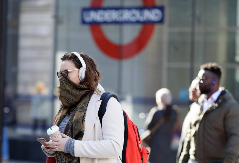 A commuter covers her face in London, Monday, March 16, 2020. For most people, the new coronavirus causes only mild or moderate symptoms, such as fever and cough. For some, especially older adults and people with existing health problems, it can cause more severe illness, including pneumonia. (AP Photo/Kirsty Wigglesworth)