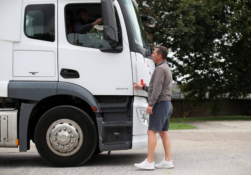 FILE PHOTO: Instructor Andy Hawes with trainee Lloyd Henry during a lesson in an articulated lorry at the National Driving Centre, Croydon, Britain, August 31, 2021.  REUTERS/Peter Cziborra/File Photo