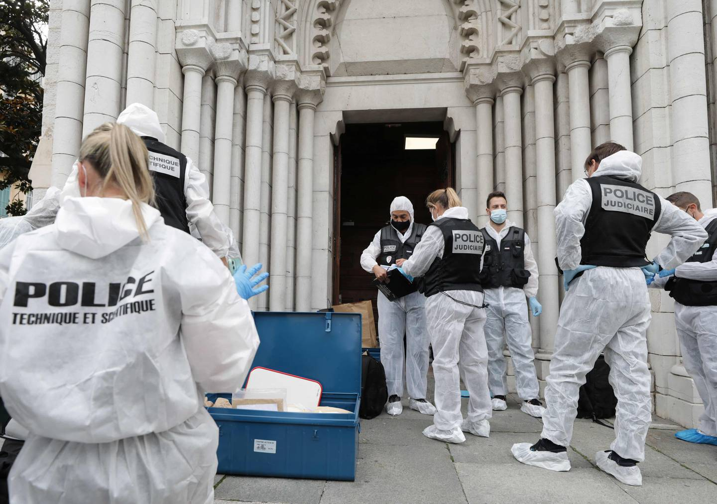 """French forensics officers operate outside the Basilica of Notre-Dame de Nice after a knife attack in Nice on October 29, 2020. - France's national anti-terror prosecutors said Thursday they have opened a murder inquiry after a man killed three people at a basilica in central Nice and wounded several others. The city's mayor, Christian Estrosi, told journalists at the scene that the assailant, detained shortly afterwards by police, """"kept repeating 'Allahu Akbar' (God is Greater) even while under medication."""" He added that President Emmanuel Macron would be arriving shortly in Nice. (Photo by ERIC GAILLARD / POOL / AFP)"""