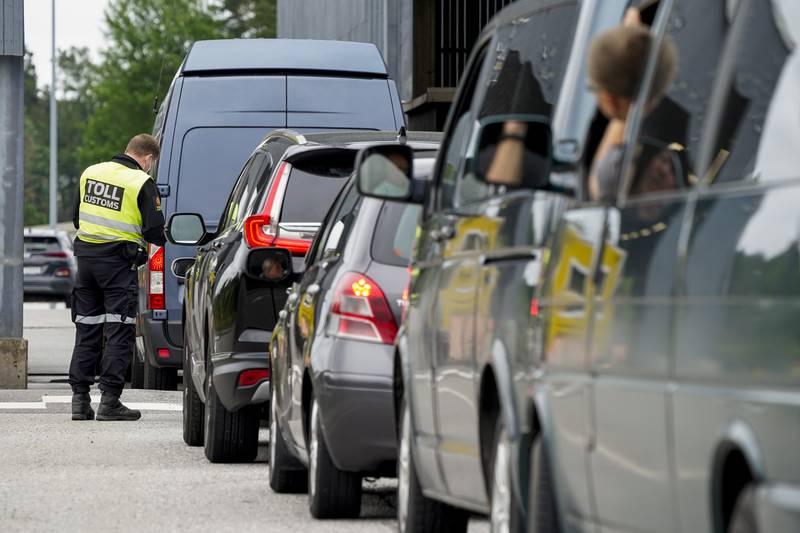 Bildet er tatt bak fra siden av biler som står i kø ved Svinesund. En toller snakker med en person i en av bilene fremst i bildet. Foto: Torstein Bøe / NTB