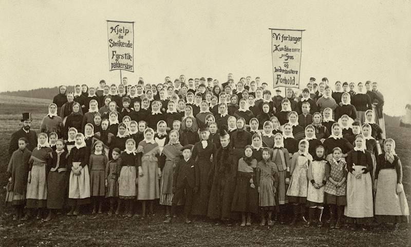 Mannen i flosshatt til venstre antas å være Carl Jeppesen. Det er usikkert hvem de to pent antrukne  kvinnene midt i bildet er. Typisk antrekk for arbeiderskene var kjole med strie forkle over, strikkesjal over skuldrene og i kryss rundt brystet, skaut på hodet og trebånner på føttene. FOTO: UKJENT PERSON/ARBARK