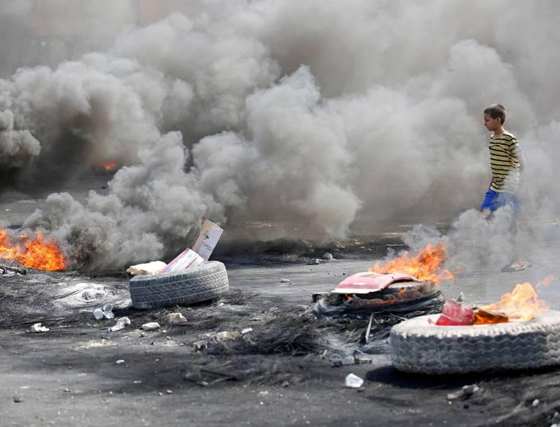 En ung gutt går mellom brennende dekk i Bagdad. Etter dager med demonstrasjoner mot landets regjering, er det innført portforbud i hovedstaden. FOTO: WISSM AL-OKILI