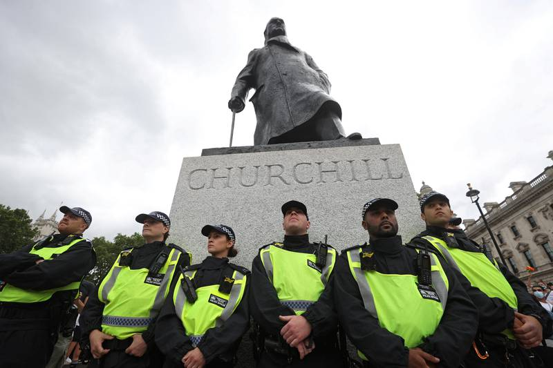Police officers guard a statue of Winston Churchill as people take part in a Black Trans Lives Matter rally in London, Britain, June 27, 2020. REUTERS/Simon Dawson