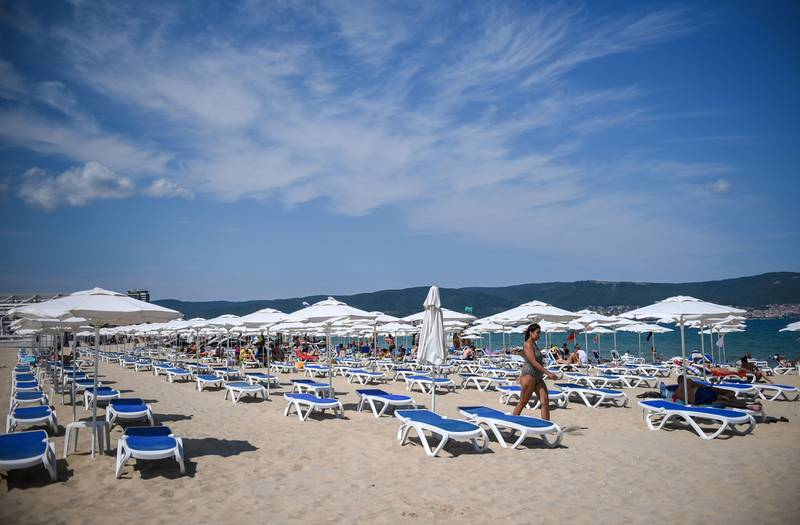 A photograph taken on July 16, 2020 shows a tourist walking near empty sunbeds and umbrellas at the beach in Sunny Beach, Bulgaria's biggest Black Sea resort. - Bulgaria is the poorest country in the EU and will be dealt a body blow by the virtual collapse of its tourism sector, which accounts for 12 percent of annual economic output. Initially Bulgaria managed to control its infection numbers but after easing its lockdown comparatively early, it has found itself in the midst of a fresh spike in infections. (Photo by NIKOLAY DOYCHINOV / AFP)