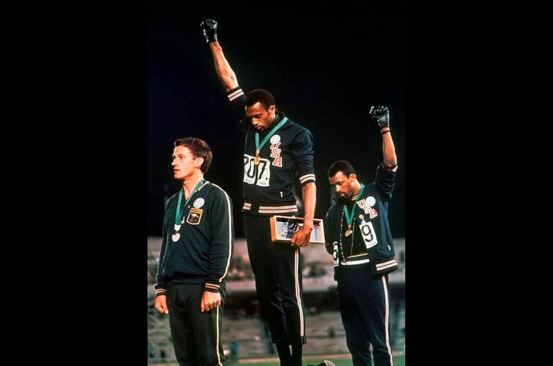 FILE - In this Oct. 16, 1968 file photo, U.S. athletes Tommie Smith, center, and John Carlos raise their gloved fists after Smith received the gold and Carlos the bronze for the 200 meter run at the Summer Olympic Games in Mexico City. The International Olympic Committee published guidelines Thursday, Jan. 9, 2020 specifying which types of athlete protests will not be allowed at the 2020 Tokyo Games. Athletes are prohibited by the Olympic Charter's Rule 50 from taking a political stand in the field of play — like the raised fists by American sprinters Tommie Smith and John Carlos at the 1968 Mexico City Games. (AP Photo, file)
