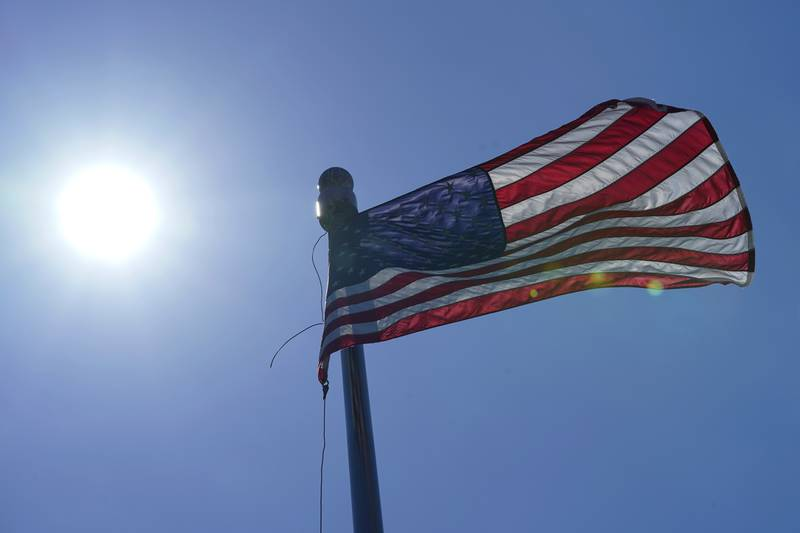 A U.S. flag flies with the sun in the background, Wednesday, June 30, 2021, in downtown Seattle. Temperatures cooled considerably in western Washington, Oregon and British Columbia Wednesday after several days of record-breaking heat, but the interior regions of the region were still sweating through triple-digit temperatures as the weather system moved east. (AP Photo/Ted S. Warren)
