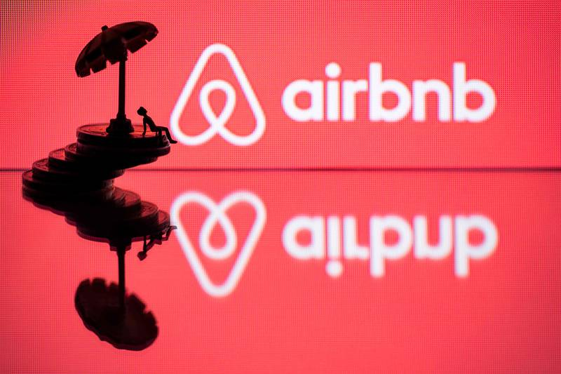 (FILES) In this file photo illustration taken on August 29, 2018 in Paris on August 29, 2018, a toy umbella and a figurine on coins sre seen next to the logo of  rental website Airbnb. - Airbnb has suffered a humiliating election defeat in Jersey City, which voted overwhelmingly to clamp down on the home sharing company's activities in the New York City suburb. Around 70 percent of the 270,000 residents in Jersey City, New Jersey -- which is separated from Manhattan by the Hudson River -- voted in favor of severe restrictions on locations that offer short-term stays, according to results released on November 6, 2019. (Photo by JOEL SAGET / AFP)