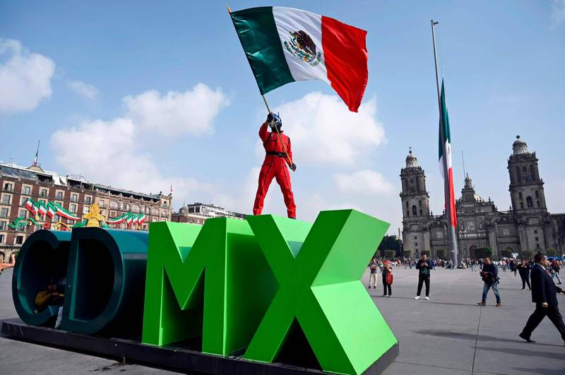 A rescueer poses with a Mexican flag at the Zocalo square in Mexico City on September 19, 2019, during an earthquake drill as Mexico marks the anniversaries of two deadly earthquakes that hit the country -one two years ago that claimed 369 lives, and another that killed more than 10,000 people on the same date in 1985. - Two years ago, residents of Mexico City had just finished the earthquake drill they hold every September 19 -- a ritual in memory of 1985 -- when, some two hours later, the ground started shaking violently. (Photo by ALFREDO ESTRELLA / AFP)