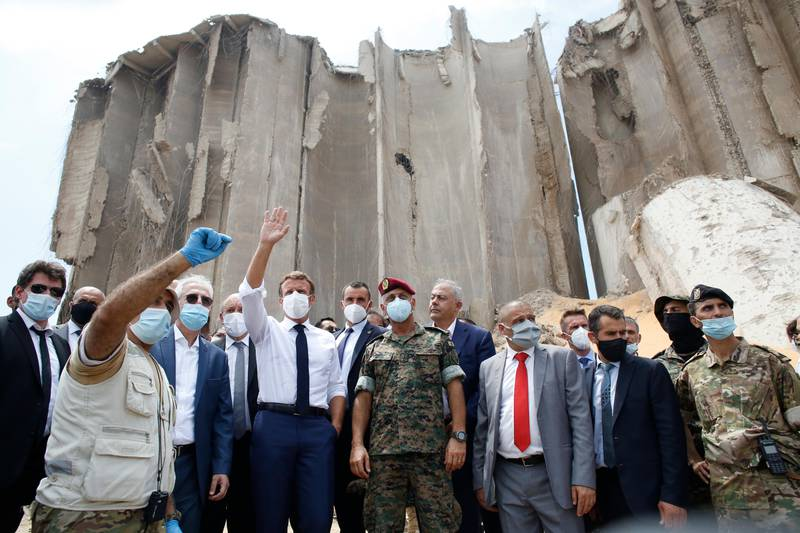 FILE - In this Aug. 6, 2020 file photo, French President Emmanuel Macron, center left, gestures as he visits the devastated site of the Aug. 4 explosion at the port of Beirut, Lebanon. An economic meltdown, a revolution, financial collapse, a virus outbreak and a cataclysmic explosion that virtually wiped out the country's main port. The past year has been nothing short of an earthquake for tiny Lebanon, with an economic meltdown, mass protests, financial collapse, a virus outbreak and a cataclysmic explosion that virtually wiped out the country's main port. Yet Lebanese fear even darker days are ahead. (AP Photo/Thibault Camus, Pool, File)