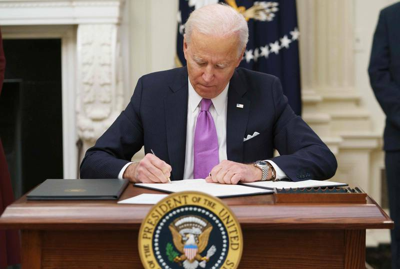 US President Joe Biden signs executive orders as part of the Covid-19 response in the State Dining Room of the White House in Washington, DC, on January 21, 2021. (Photo by MANDEL NGAN / AFP)