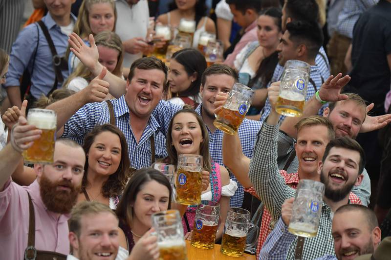 People in traditional Bavarian dress raise their beer glasses in a beer tent at the Oktoberfest beer festival in Munich, southern Germany, on September 22, 2019. - The world's biggest beer festival Oktoberfest will be running until October 6, 2019. (Photo by Tobias SCHWARZ / AFP)